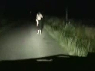 A movie of a girl stripping infront of a car for a ride. She is shown off by the headlights and it furns out to be a great time for both her and the guy driving