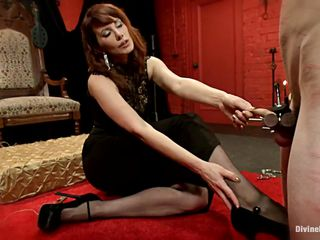 Divine Madeline takes off her high heels and plays with her feet on the guy's cock. She putted his dick in a special bondage device and squeezed it real hard so now she can play and do what she wants with him. Look at her biting the balls and dominating the male, that excites her a lot so she get's off with a vibrator