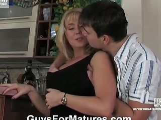 Seductive golden-haired aged sweetheart tempting a guy into a sexy quickie by the bar