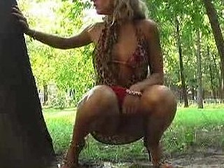 Sexy blond sweetheart piddling behind a tree