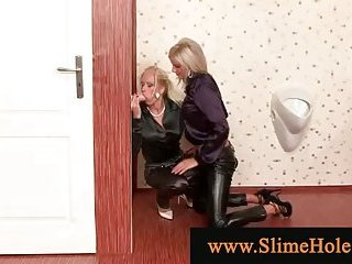 Blonds receive bukkake through gloryhole