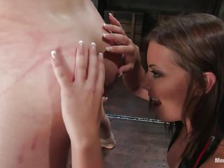 Penny Flame has her slave Max tied by his hands and feet and even has a rope connected to the floor, tied to his dick! She has whipped him so hard he's welted, cut, and bleeding slightly. Still, he loves it. She exchanges one type of whip for another and whacks his legs, kissing his cock to be nice.