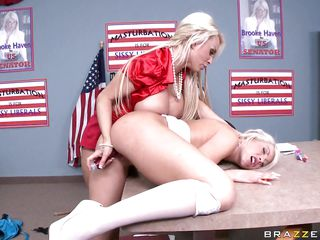 Brooke Haven campaigned on masturbation, and Holly Halston is furious. She says real American women don't fuck themselves and Brooked ruined her career. Holly is punishing Brooke, who's bent over a table, with a dildo. Then she gets a bigger one from her briefcase, straps it on and starts to fuck