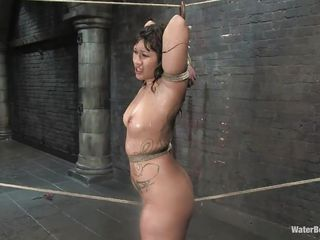 Her shaved vagina looks great with that long rope between it. Her hands are tied and the rope between her pussy lips keeps this brunette milf in one place until the executor arrives and gives her a some intense penetration with that dildo. She likes to be treated roughly and that is exactly what she deserves and gets.